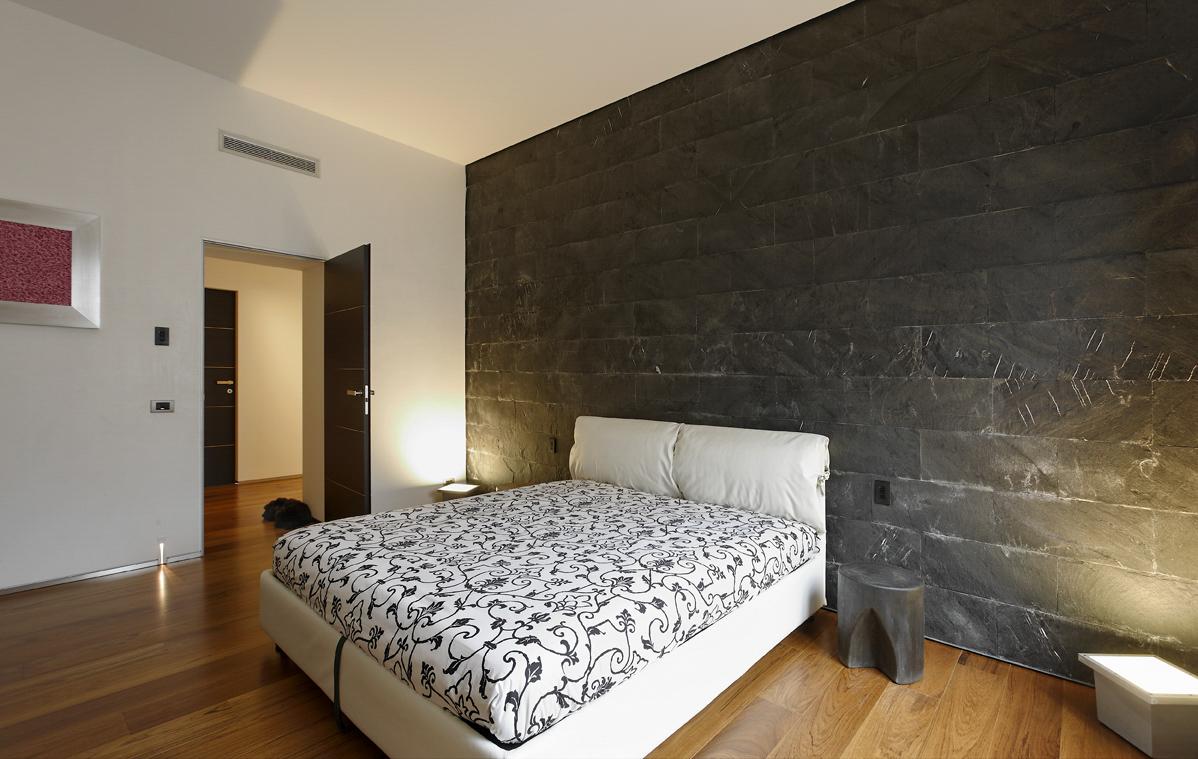 Camera da letto con rivestimento parete in ardesia nera a ...